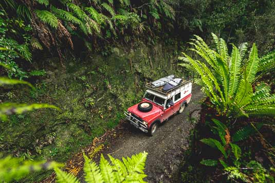 Driving the Deuce Land Rover through hidden New Zealand native forestry and tunnels, Adventure Photography