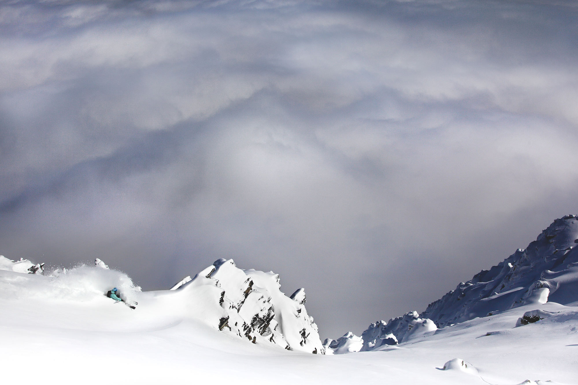 Free Skier Pete Oswald Skiing powder above clouds up The Remarkables