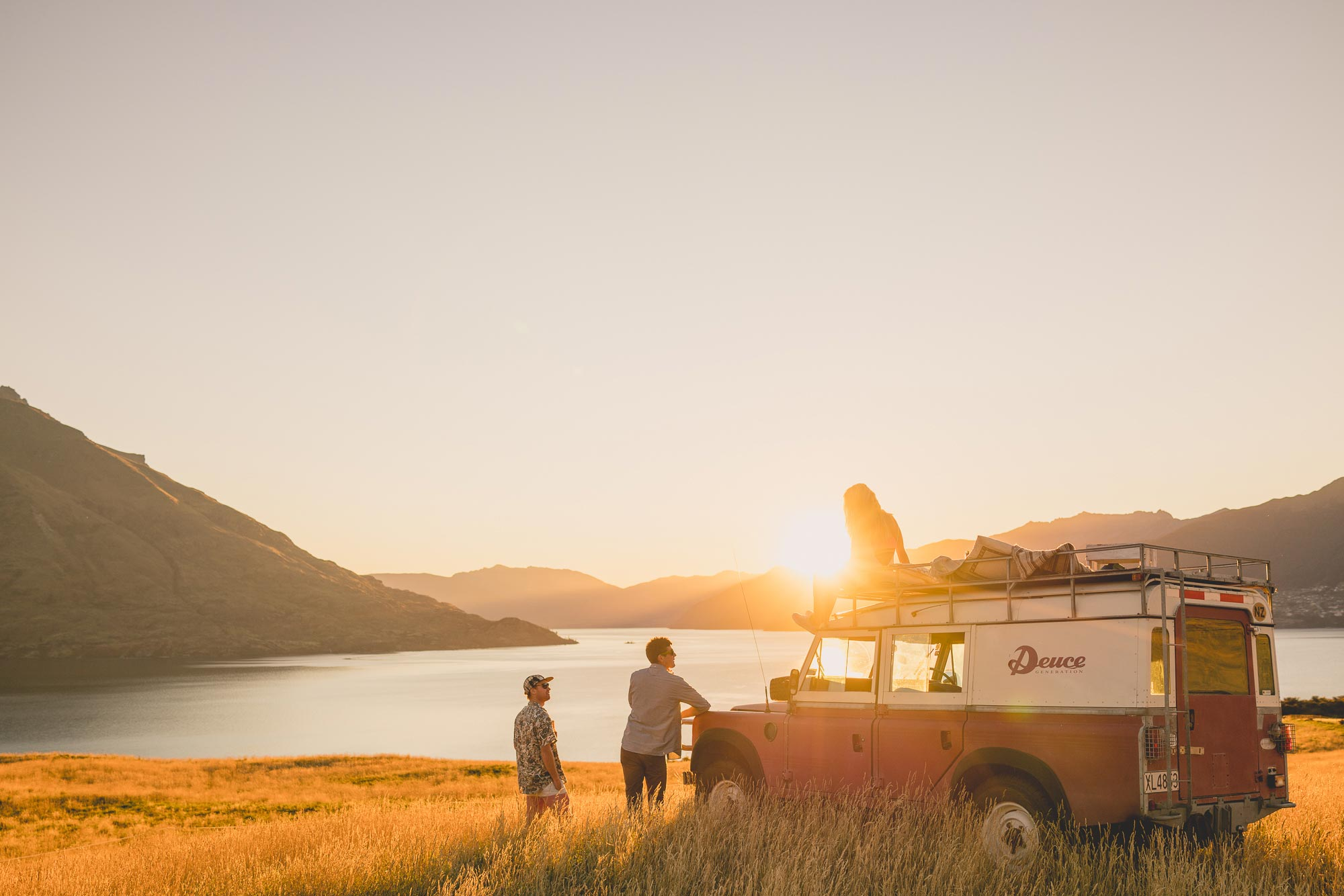 Friends watching the sunset with the Deuce land Rover in Queenstown