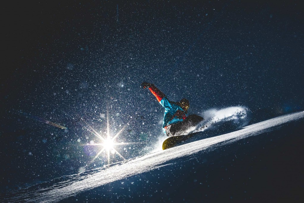 Josh Clark snowboarding at night in fresh powder up Coronet Peak, NZ