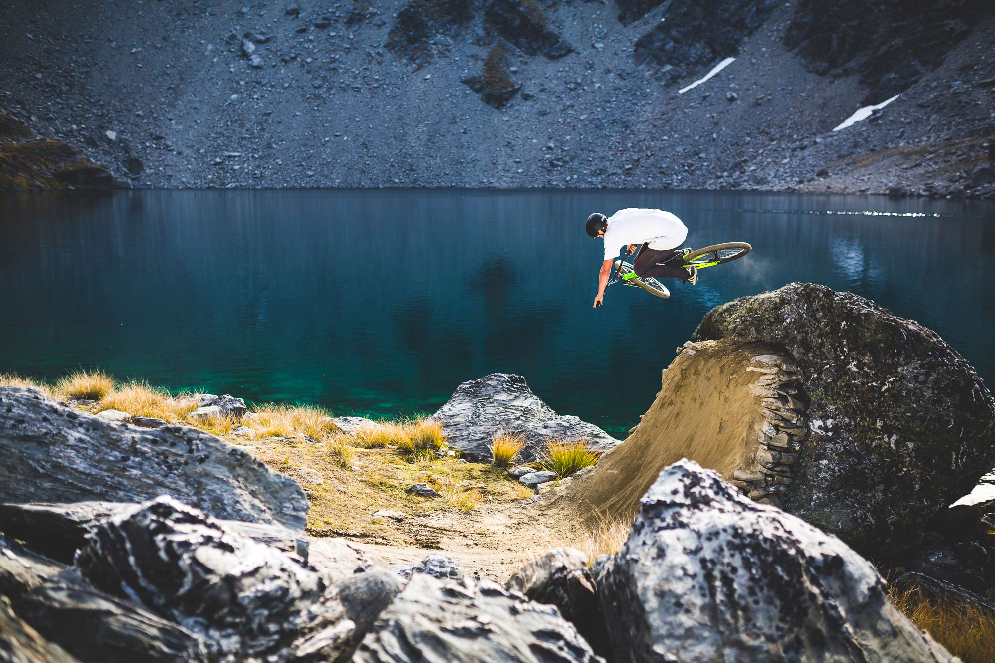 Mountain Bike rider Nick Dethridge jumping near alpine lake in Queenstown