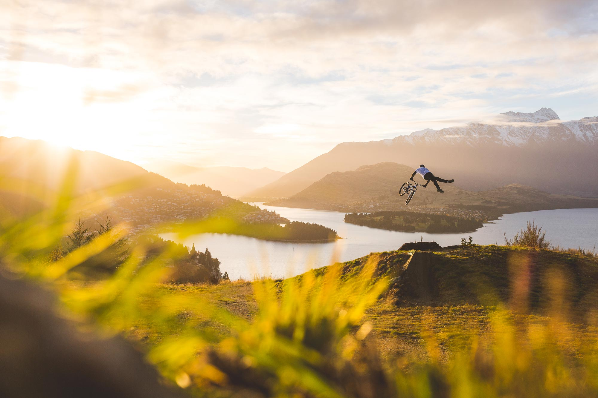 Mountain bike rider Emmerson Wilkins super whips jump overlooking Queenstown at sunrise
