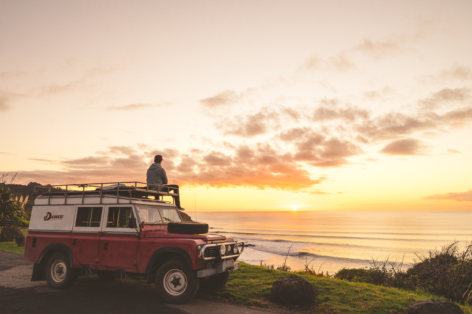 Sitting on top of the Deuce Sneakers Land Rover looking at the surf in Raglan, NZ