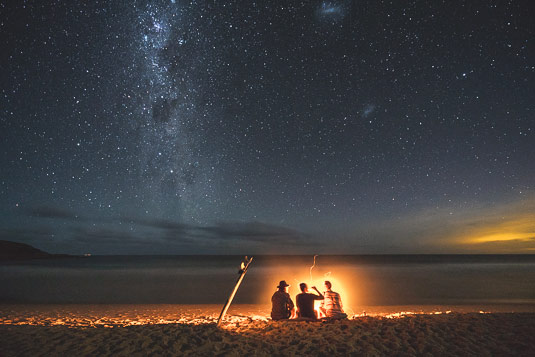 Surfers enjoying drinks under the stars around a campfire in Australia, lifestyle Photography