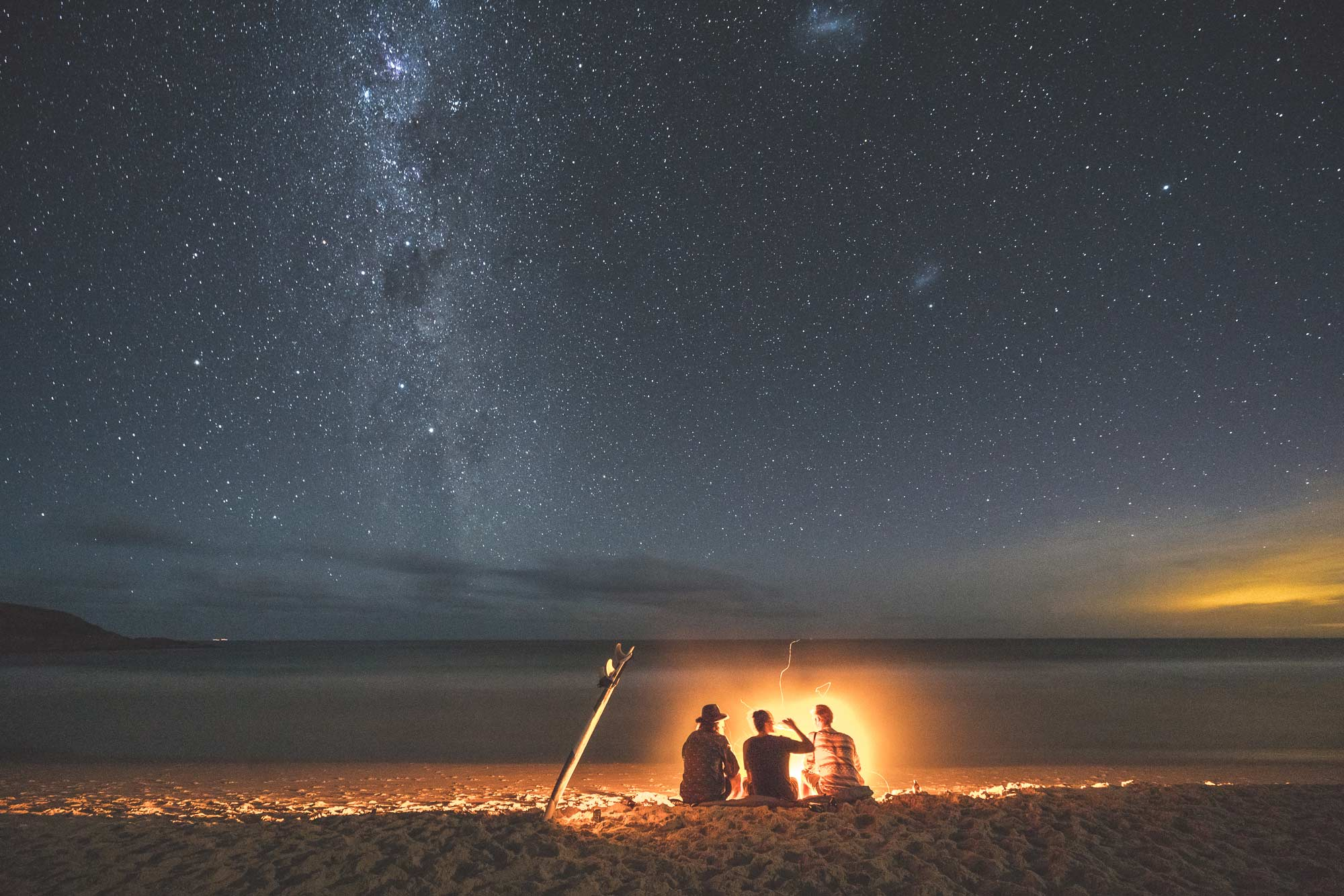 Surfers enjoying drinks under the stars around a campfire in Australia