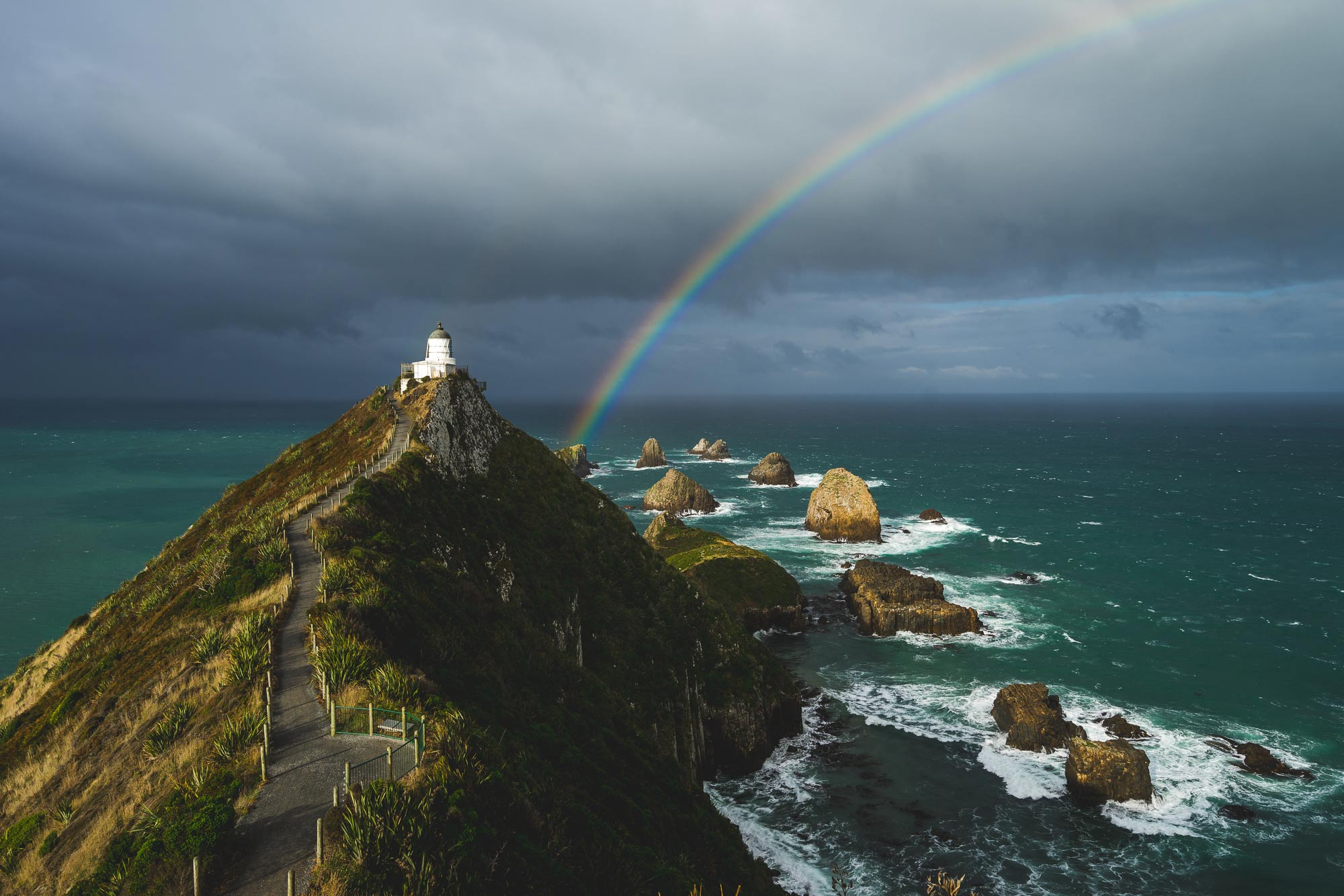 Rainbow over Nugget Point lighthouse in Catlins, NZ
