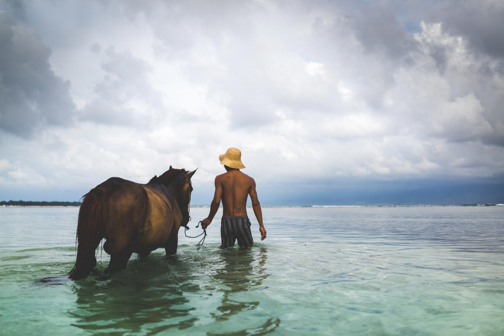 Balinese taking his horse in the ocean to wash