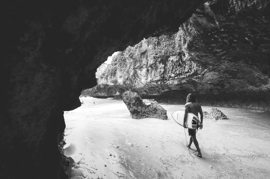 Surfer Joe going through the uluwatu cave to get to the beach, Bali