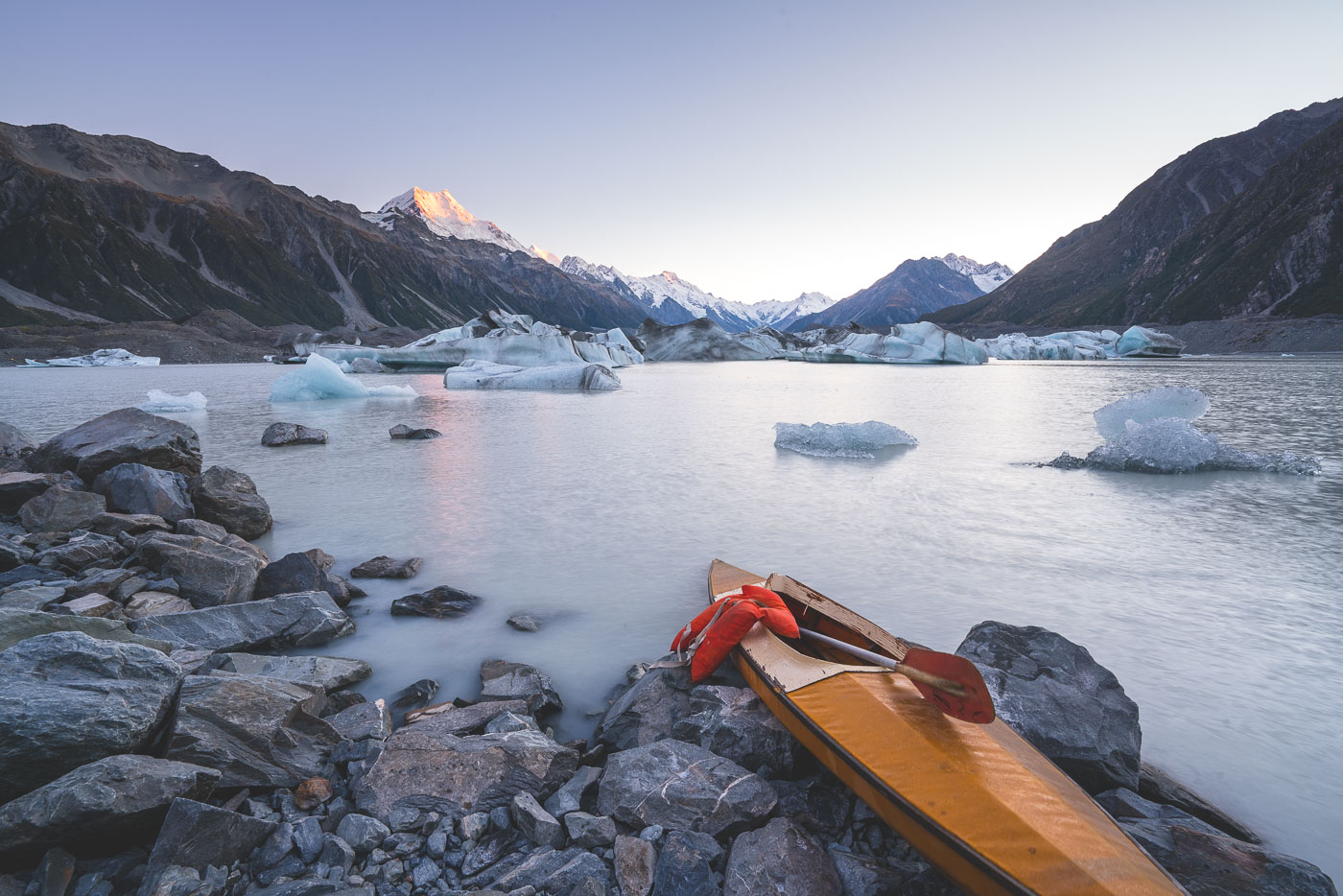 Kayak on the shores of Tasman Lake with Mount Cook in the background at sunrise