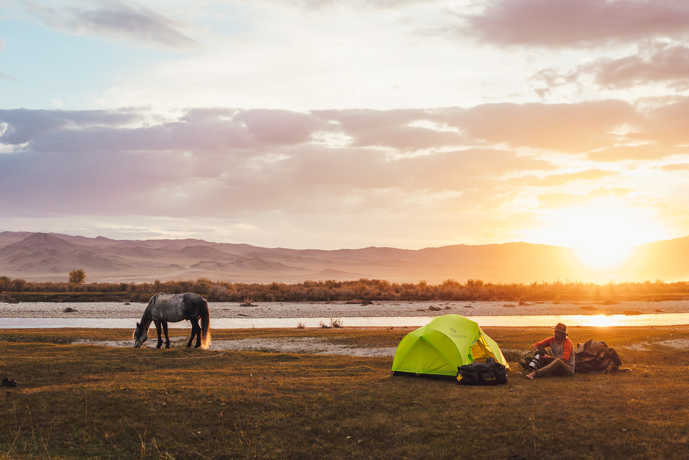 Solo horse trekking trip through Mongolia, Stefan Haworth looking through images at the campsite at sunset