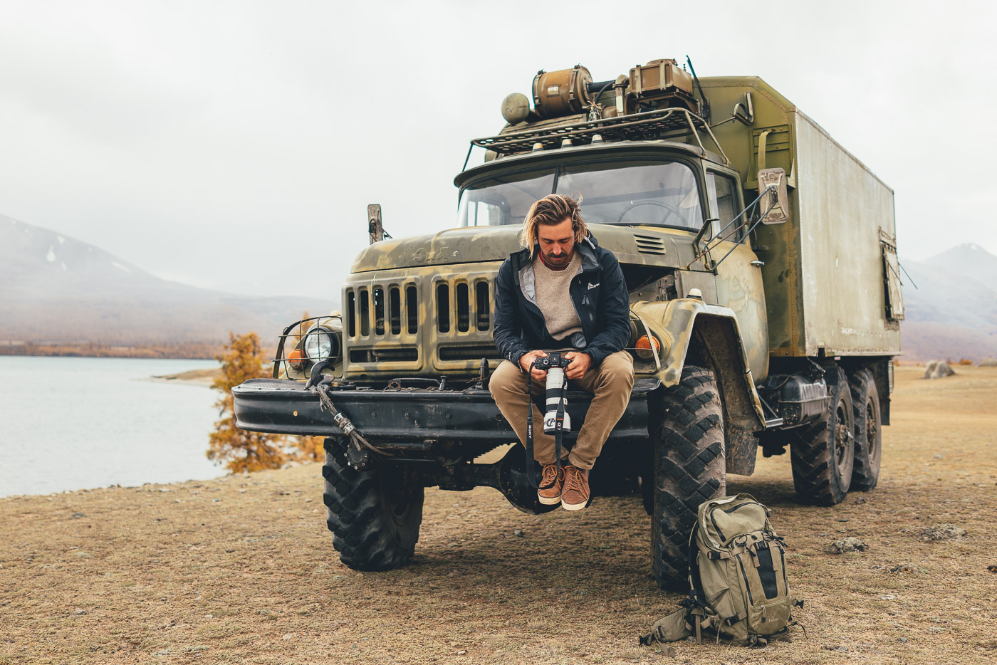 Stefan Haworth sitting on army truck and reviewing images in Mongolia with Sony a7rII and FE 70-200mm f/4 G OSS