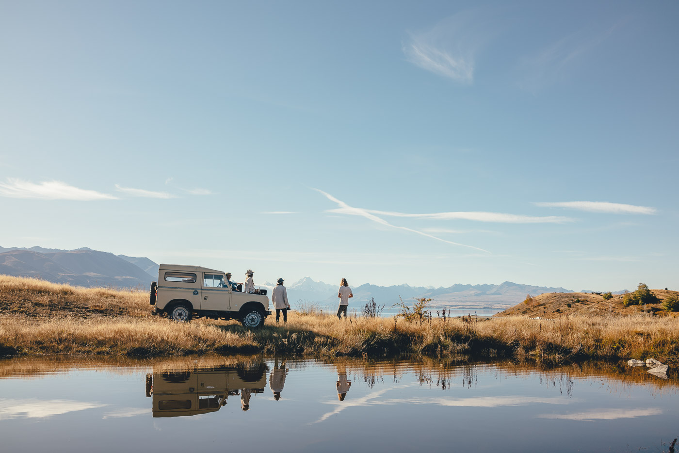 Friends sitting on the Land Rover enjoying the views over Lake Pukaki