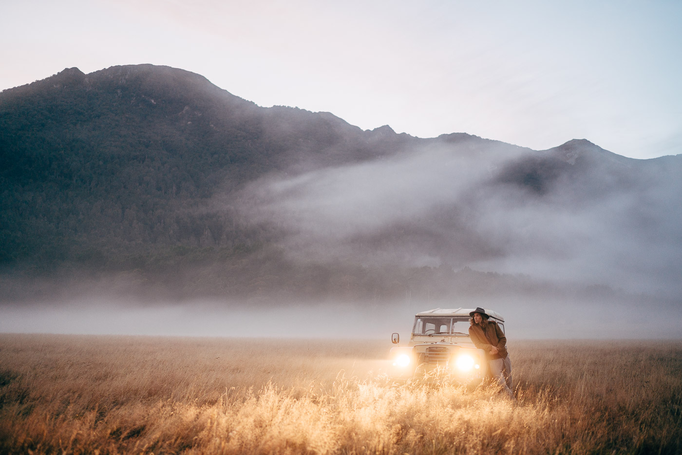 Land Rover in a grass field in the fod of Fiordland, New Zealand