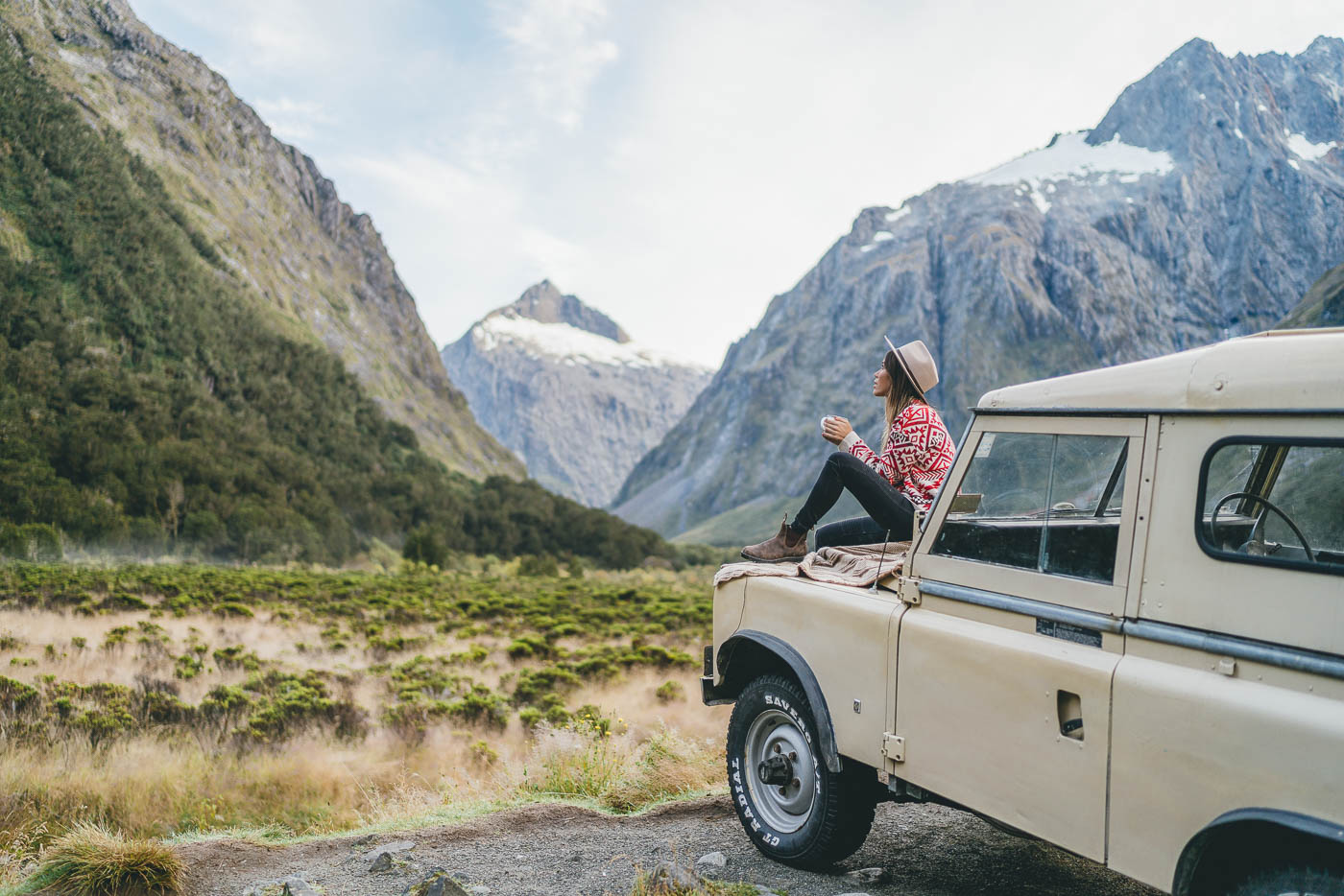 Enjoying a hot drink on a vintage Land rover in Fiordland, New Zealand