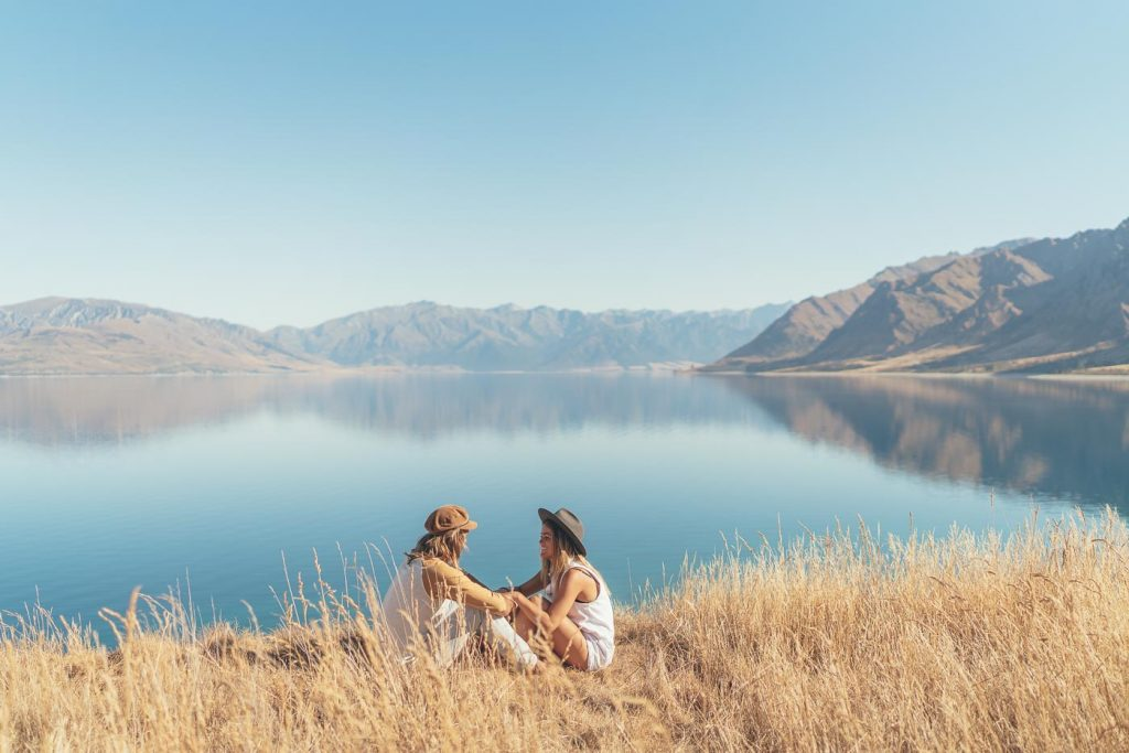 Photographer Stefan Haworth and Jess Davis sitting on the bank of Lake Hawea in New Zealand on the Will and Bear Road trip