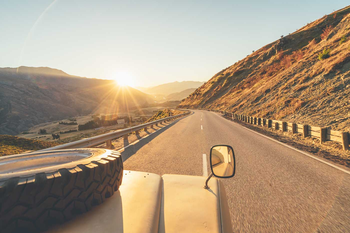 Land Rover driving over crown range at sunset in New Zealand