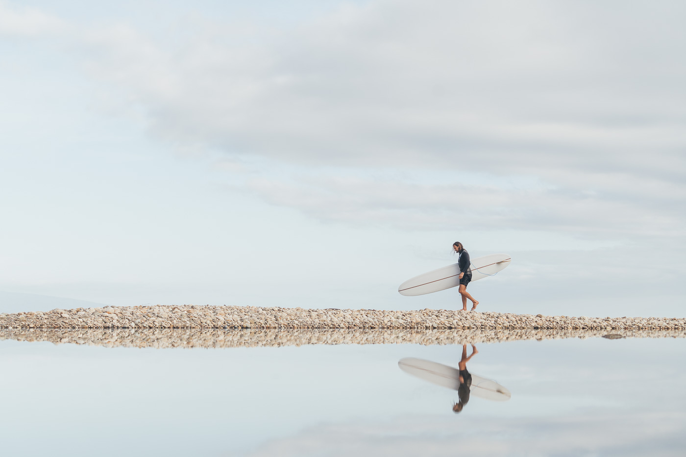 Reflection of Surfer carrying Surfboard to the beach in New Zealand