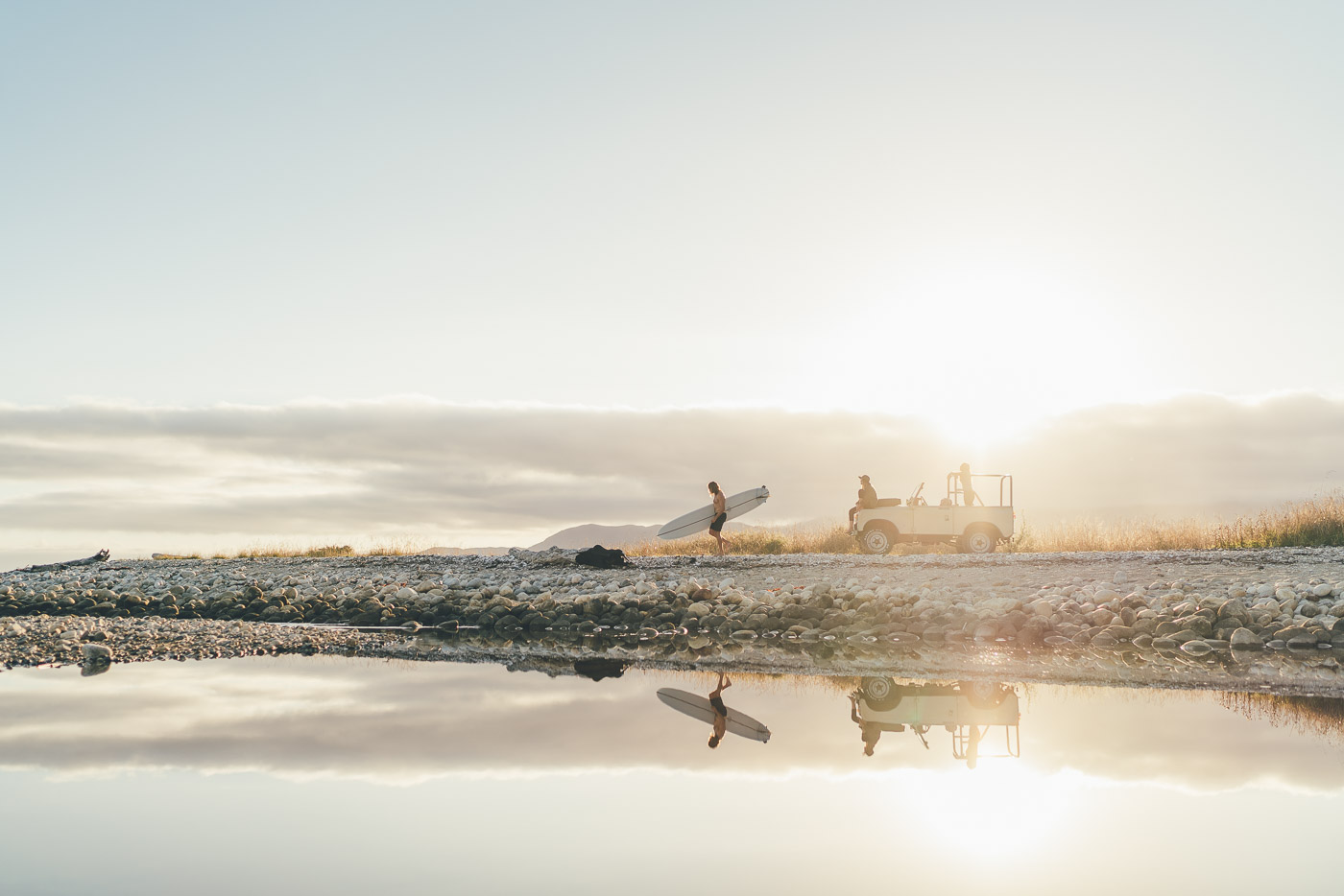 Reflection of Surfer carrying Surfboard from land Rover to the beach in New Zealand