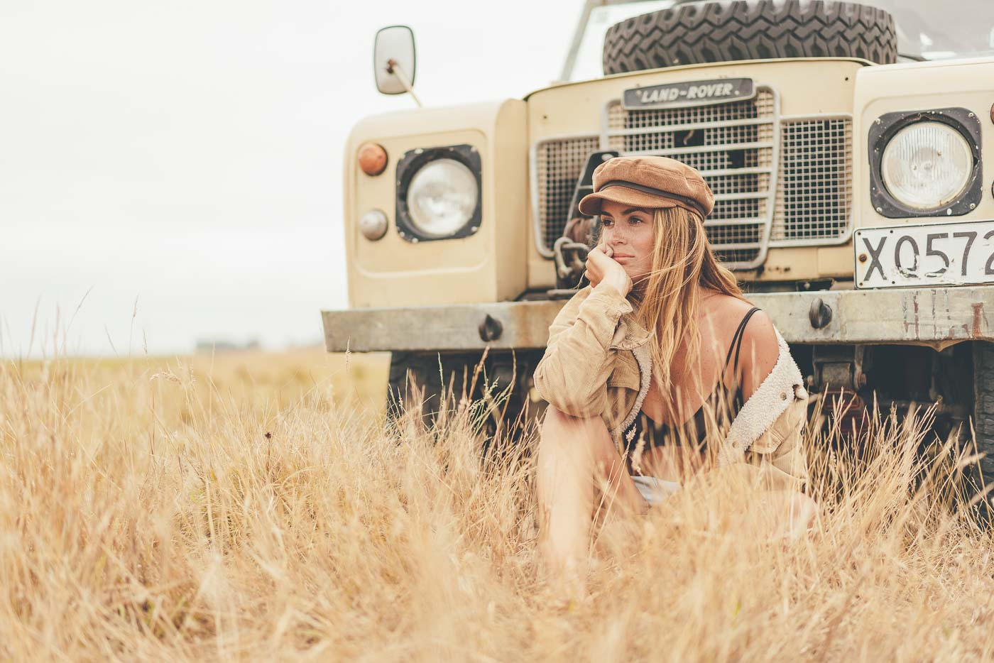 Jess Davis sitting in long grass in front of land rover