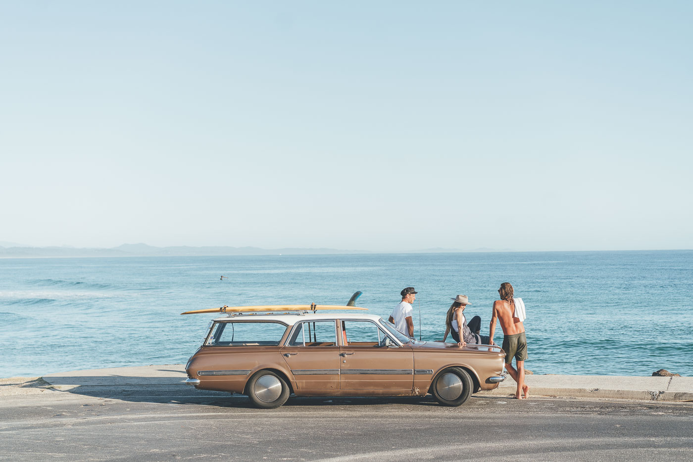 Friends hanging out at Byron bay with vintage car