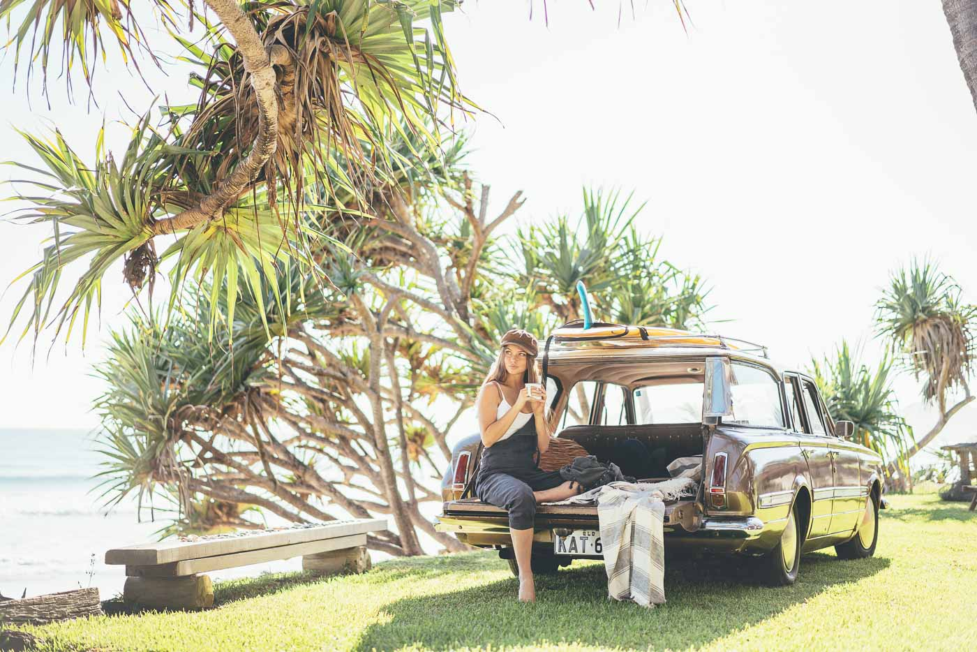 Girl sitting on the boot of the vintage car drinking coffee