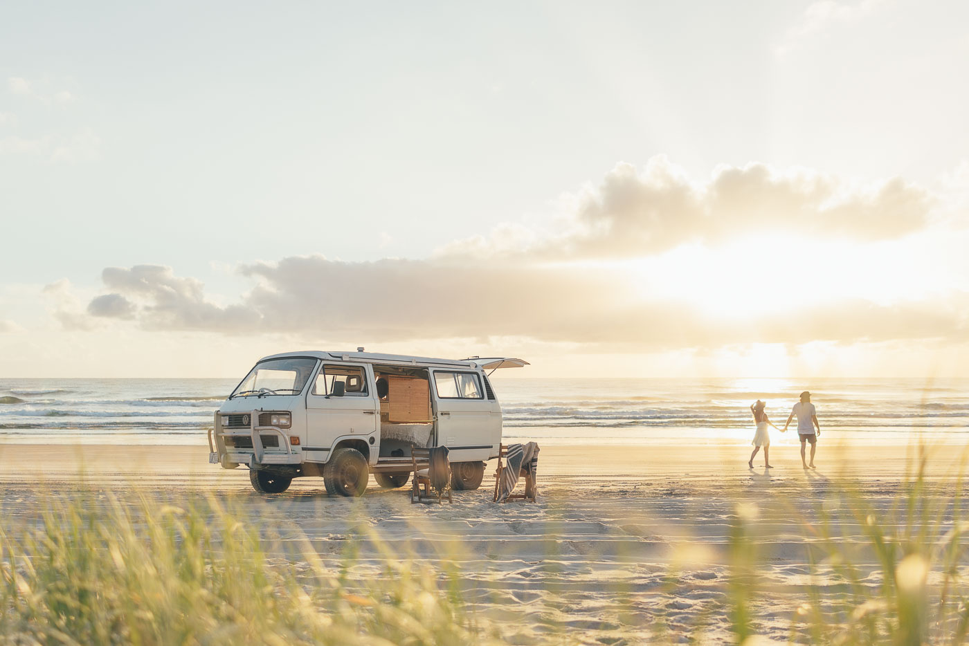 Couple parked on the beach going for a walk at sunrise