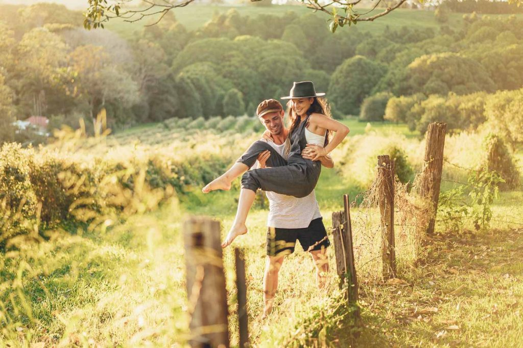 guy lifting girl over a fence at sunset