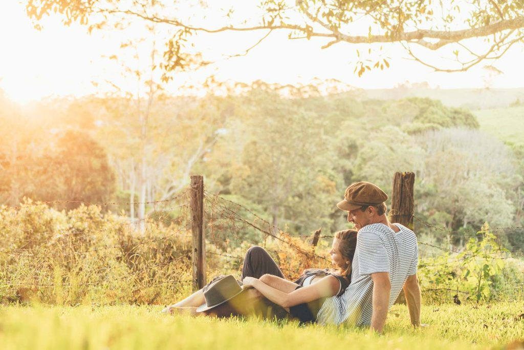 Couple in grass at sunset