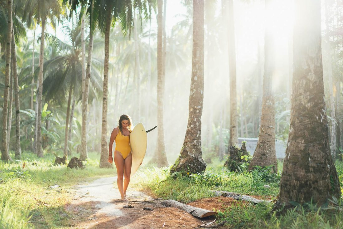Jess davis carrying a longboard through coconut palm trees, Philippines